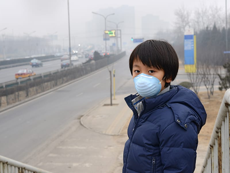 Child with anti-smog mask
