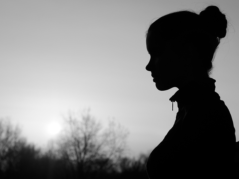 Silhouette of girl in nature summer sunset