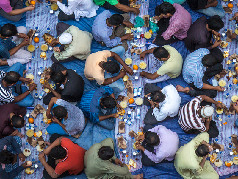 Muslim men gathering for a communal charity iftar organised on a street by a local mosque