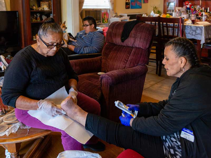 Patricia Zamora's grandmother helps clean her wound.