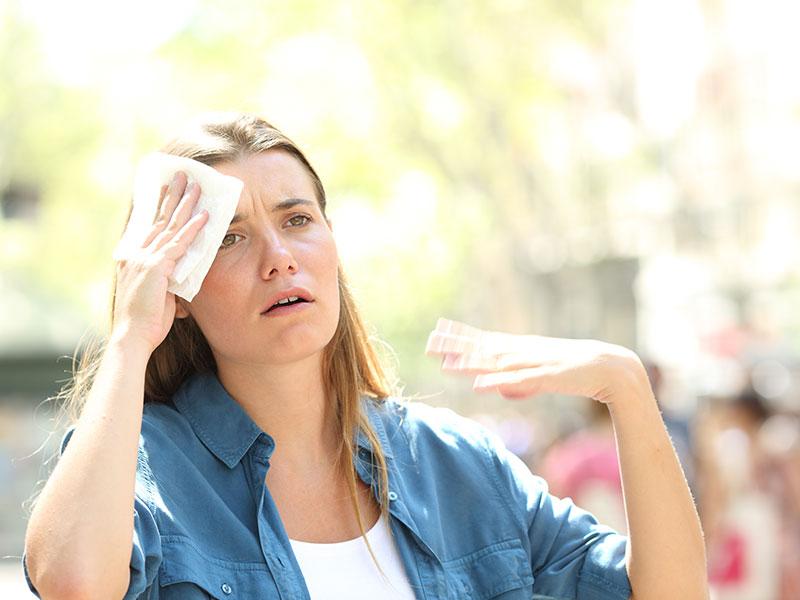 Unhappy woman sweating suffering a heat stroke