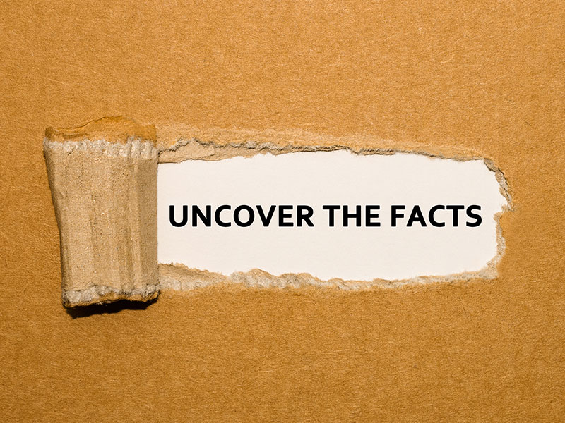 Uncover the facts text on brown paper background