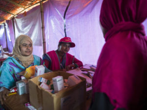 Volunteers hand out medicine to refugees